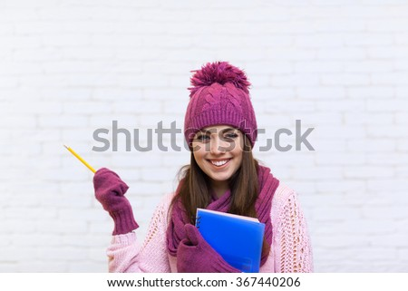 Attractive Student Girl Hand Gesture To Copy Space Smile In Pink Hat Holding Folder Pencil Over White Brick Background - stock photo