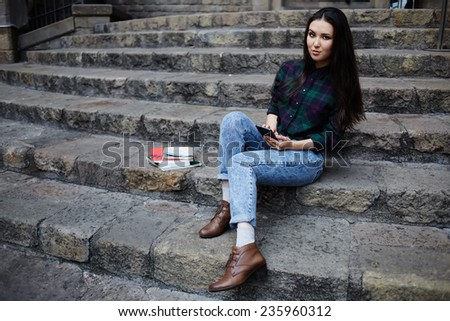 Attractive student girl holding smart-phone looking to the camera, asian race student girl browsing the internet with her cell phone during class break at university school, technology concept - stock photo