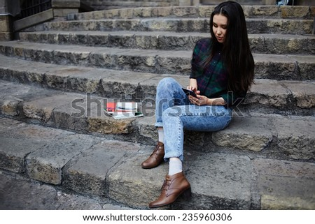 Attractive student girl using a smart phone sitting on the steps outdoors, asian race student girl browsing the internet with her cell phone during class break at university school, technology concept - stock photo