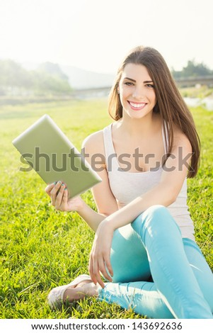 Attractive student in nature holding digital tablet - stock photo