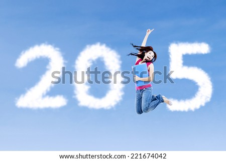 Attractive student jumping on the sky and forming number 2015 - stock photo