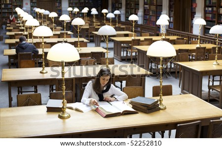 Attractive student sitting at desk in old university library and studying books. - stock photo