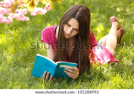 Attractive student teen girl reading book on green spring grass - stock photo