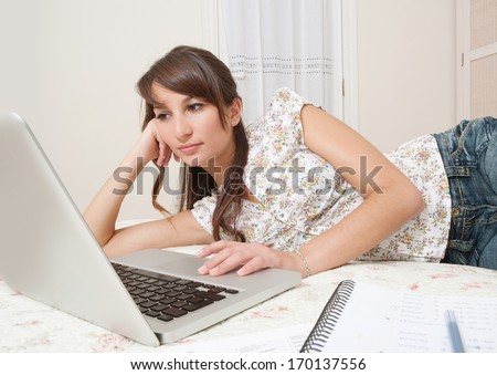 Attractive student woman laying down on her bed at home using a laptop computer while working on her homework for college, preparing for exams. Studying in a home interior.