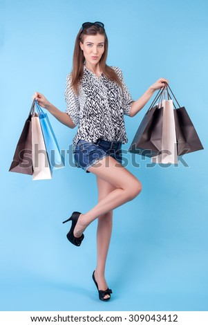 Attractive styled woman is going shopping with joy. She is carrying many packets and showing it with proud. The lady is posing and looking at the camera happily - stock photo
