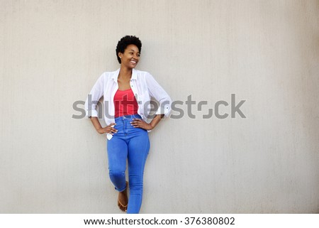 Attractive stylish african woman standing with her hands on her hips looking away at copy space with a smile - stock photo