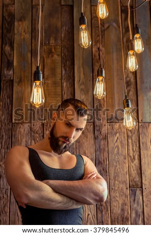 Attractive stylish man with beard in black singlet looking at camera, standing on a wooden background - stock photo
