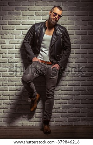 Attractive stylish man with beard in leather jacket and sunglasses looking at camera, standing against brick wall - stock photo