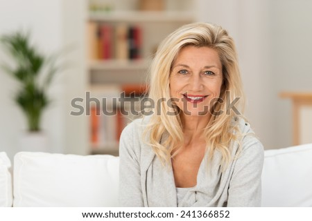 Attractive stylish middle-aged blond woman sitting on a sofa in her living room smiling at the camera, head and shoulders portrait - stock photo