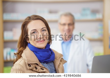 Attractive stylish middle-aged woman with a lovely smile standing looking at the camera in a pharmacy with a male pharmacist visible as a blur behind