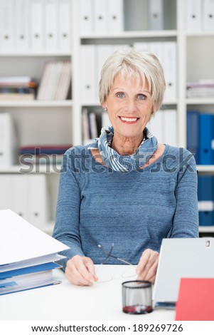 Attractive stylish senior manageress sitting in her office surrounded by business files and paperwork smiling at the camera - stock photo