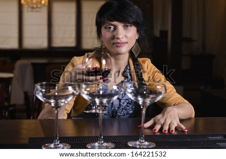 Attractive stylish woman smiling as she sits alone drinking a glass of red wine at the bar in a nightclub - stock photo