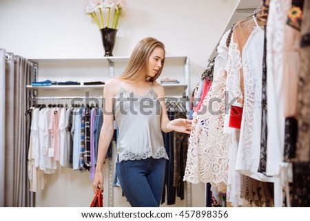 Attractive stylish young woman choosing clothes in shop - stock photo