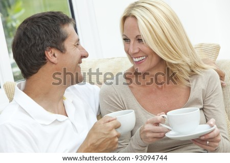 Attractive, successful and happy middle aged man and woman couple in their forties, sitting together at home on a sofa enjoying a cup or mug of tea or coffee - stock photo