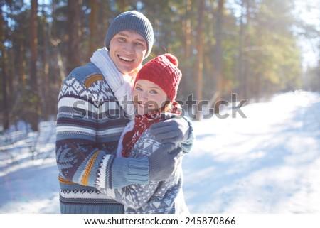 Attractive sweethearts looking at camera in natural environment - stock photo