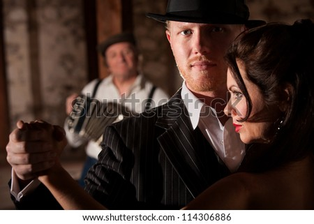 Attractive tango dancer in hat with beautiful partner - stock photo