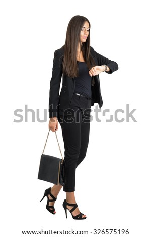 Attractive tanned business woman checking time while walking. Side view. Full body length portrait isolated over white studio background.  - stock photo
