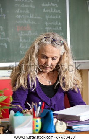 Attractive teacher at work in the classroom checking homework - stock photo