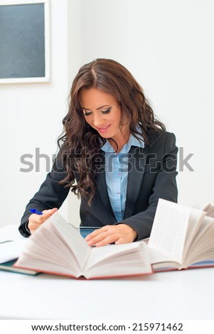 Attractive teacher checking tests at school. - stock photo