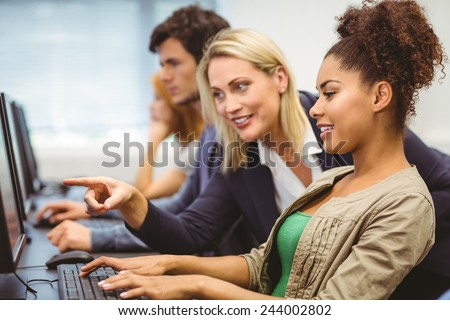 Attractive teacher talking to her student in computer class at the university - stock photo