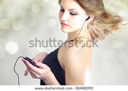 Attractive teen age girl listening to music with mp3 player and earphone with hair blowing in the wind on bokeh background - stock photo
