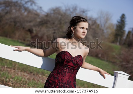 Attractive teen dressed in a mermaid style dress leaning against a white fence.  Room for your text. - stock photo