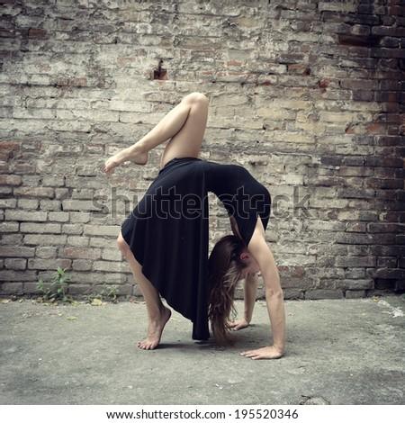 Attractive teen girl dancing outdoor against grunge bricks wall. Toned. - stock photo