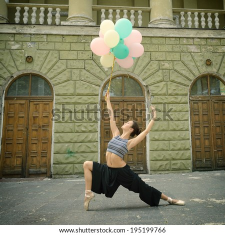 Attractive teen girl dancing outdoor in park against old building with columns holding colored balloons. Toned.