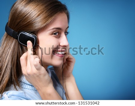 attractive teen girl listening to music on headphones, portrait over blue background with copyspace - stock photo