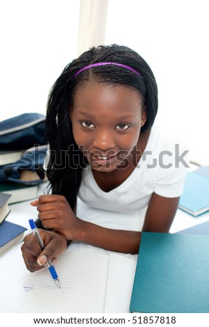 Attractive teen girl studying lying on her bed at home - stock photo