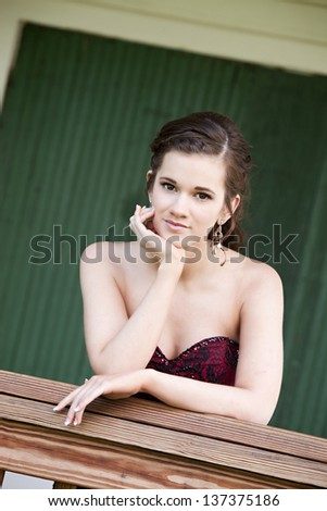 Attractive teen leaning on a railing.  Room for your text. - stock photo