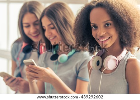 Attractive teenage Afro American girl with headphones looking at camera and smiling, in the background two other girls using phones and smiling - stock photo