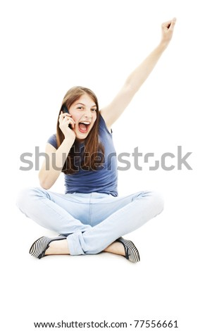 Attractive teenage girl cheering during phone call. All on white background. - stock photo