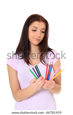 Attractive teenage girl choosing a pencil. All on white background.