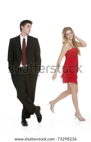 Attractive teenage girl in a red dress walking away from teenage boy in a suit - stock photo