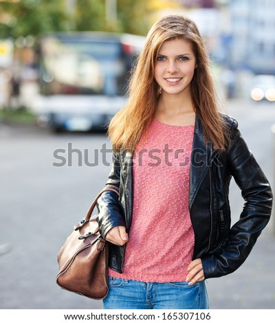 Attractive teenage girl in the city. Local bus station in the background. - stock photo