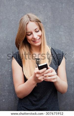 Attractive teenage girl using smart phone - stock photo