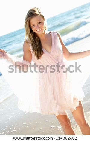 Attractive Teenage Girl Wearing Dress On Beach - stock photo