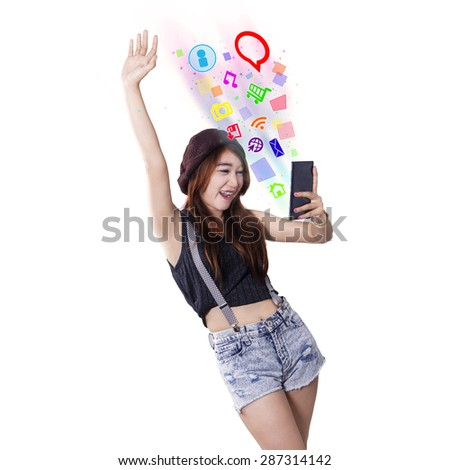 Attractive teenage girl with casual clothes standing in the studio while using social media on her mobile phone - stock photo