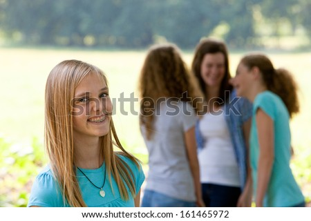 Attractive teenage girl with dental braces standing smiling broadly at the camera as her friends chat in the background