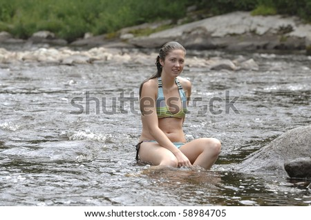 Attractive teenage girls enjoy playing in the cold mountain river. - stock photo