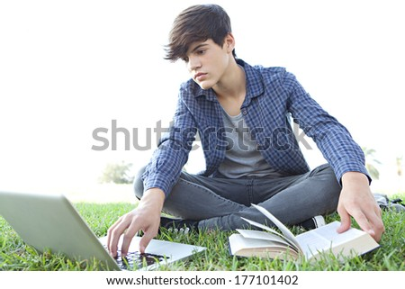 Attractive teenager boy sitting down on green grass in a park reading an open reference book and using a laptop while studying and doing his homework against a sunny sky. Outdoors lifestyle. - stock photo