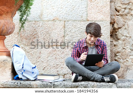 Attractive teenager boy sitting on a college campus with school books and a backpack against an old stone wall and using a digital tablet pad to do his homework. Education technology lifestyle.