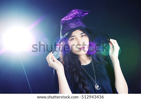 Attractive teenager wearing a witch costume.  Background light and lens flare included in image.