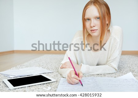 Attractive teenager with red hair and healthy freckled skin looking and smiling at the camera, while working on her course paper at home. Student girl using blank copy space tablet for doing homework  - stock photo