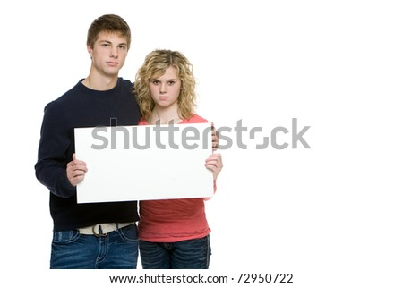 Attractive teenagers holding blank sign isolated on white background - stock photo