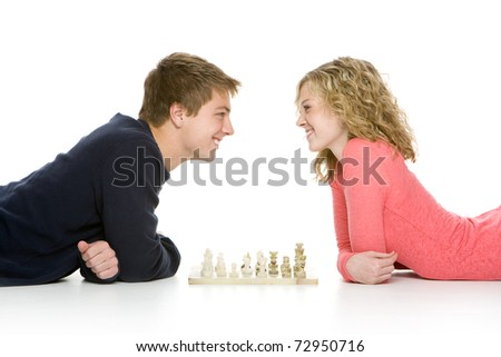 Attractive teenagers lying down using playing chess, isolated on white background