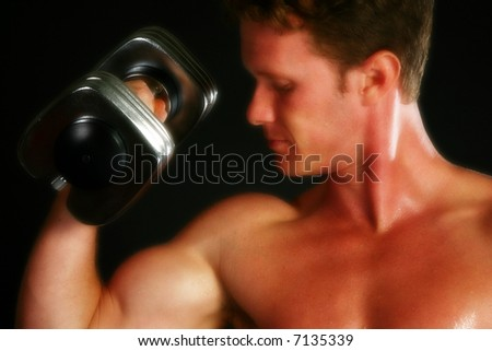 Attractive thirty something man lifting weights over black.