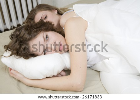 attractive thoughtful brunette curl woman with a pillow on the bed. Two women in bed. Women`s friendship