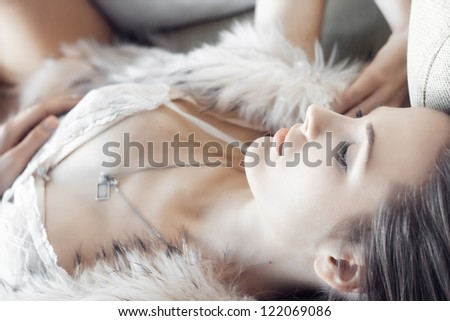 attractive thoughtful girl lying on the sofa in the sun - stock photo